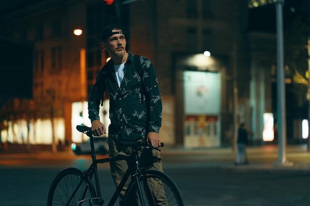 Radfahrer stehen auf der straße neben seinem klassischen fahrrad, während sie zuschauen