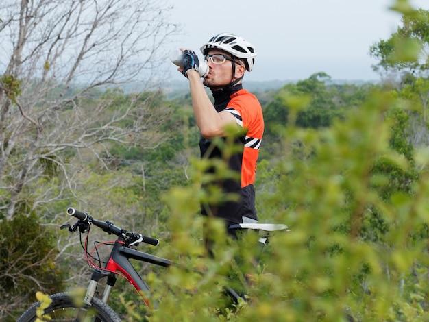 Radfahrer-trinkwasser von der wasserflasche oben auf einem berg mit meerblick. mann in einem weißen helm mit einem fahrrad trinkt wasser. mountainbike.