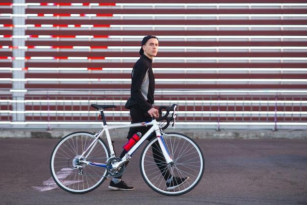 Radfahrer und cyberpunk hintergrund. fahrradfahrer auf dem hintergrund der großen leinwand.