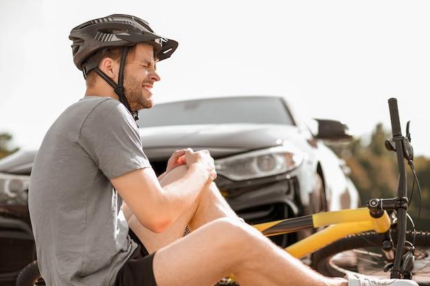 Radfahrer, verletzung. profil eines unglücklichen jungen erwachsenen radfahrers mit knieverletzung beim sturz beim sitzen auf dem boden vor dem auto am sommertag