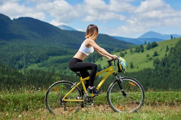Radfahrerin, die auf gelbem fahrrad auf einer ländlichen spur in den bergen reitet und talblick am sonnigen tag genießt. berge, wälder und blauer himmel outdoor-sportaktivitäten