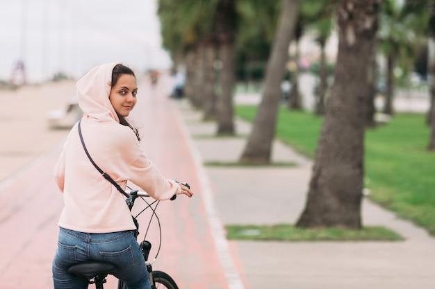 Radfahrerin, die ein fahrrad auf radweg auf der böschung reitet