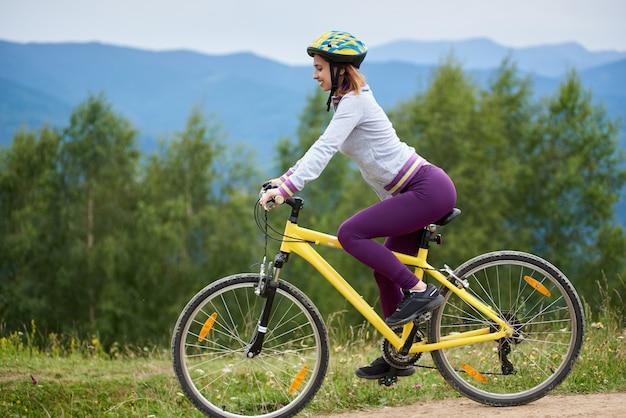 Radfahrerin, die fahrrad in den bergen radelt