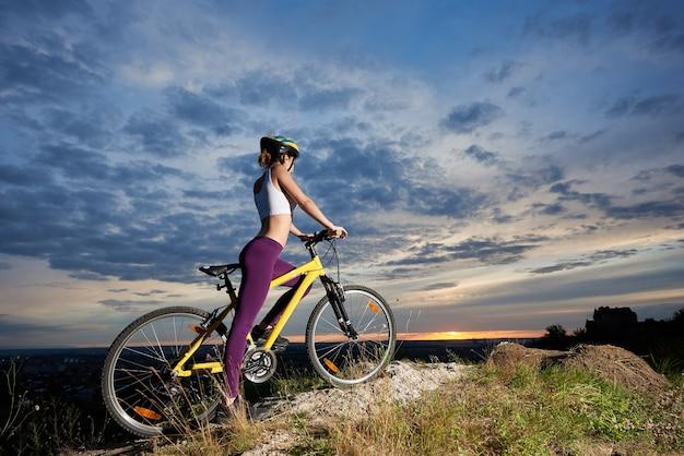 Radfahrerin, die mountainbike auf felsenhügel radelt