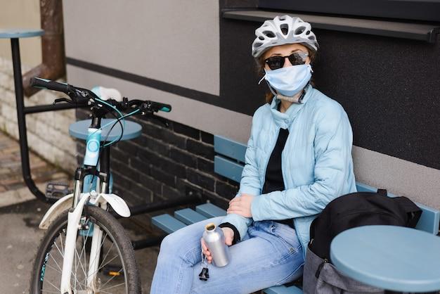 Radfahrerin im helm und in der sonnenbrille und in der medizinischen maske