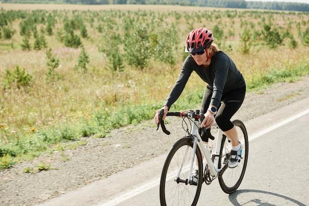 Radfahrerin mit helm, die während des sporttrainings auf einem fahrrad allein auf einer straße fährt
