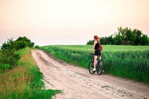 Radfahrermädchen am sonnenuntergang auf dem feld