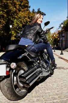 Radfahrermädchen in einer lederjacke auf einem motorrad
