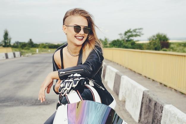 Radfahrermädchen in leder kleidet auf einem motorrad