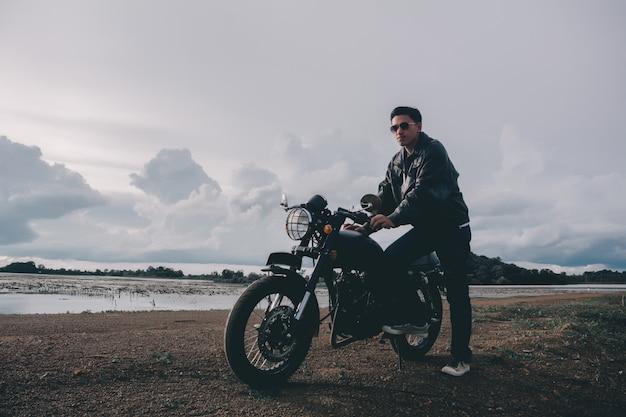 Radfahrermann mit seinem motorrad neben dem natürlichen see und schön.