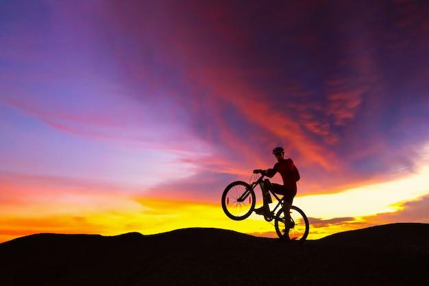 Radfahrerreitmountainbike auf der felsigen spur bei sonnenuntergang.
