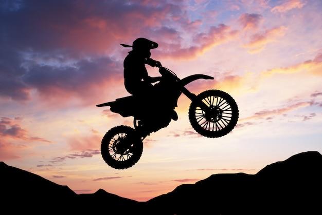 Radfahrerschattenbild, das mit seinem motocrossmotorrad springt