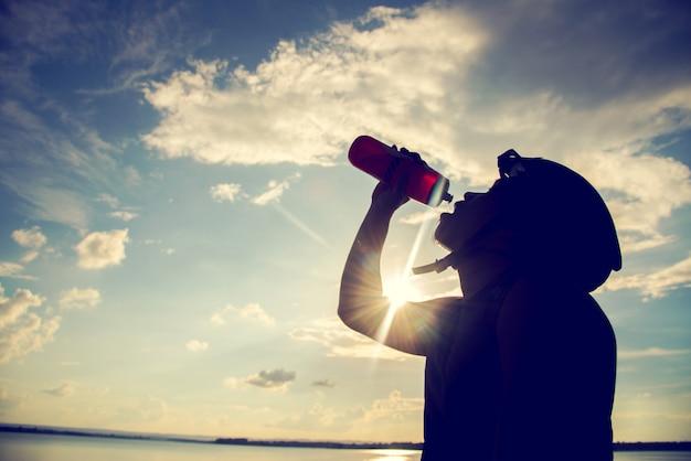 Radfahrerschattenbild des radfahrers stillstehend und des trinkwassers bei sonnenuntergang.