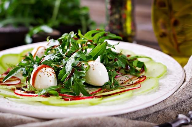 Radieschen-carpaccio mit rucola, mozzarella und balsamico-sauce. gesundes essen. daikon salat.