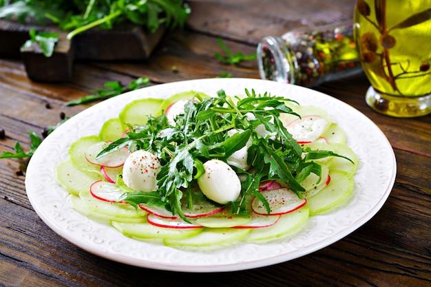 Radieschen-carpaccio mit rucola, mozzarella und soße. gesundes essen. daikon salat
