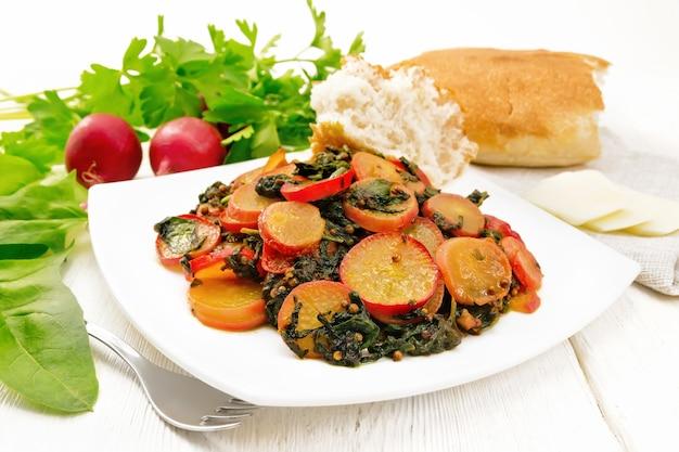 Radieschen gedünstet mit spinat und gewürzen in einem teller, käse und brot, handtuch vor hellem holzbretthintergrund