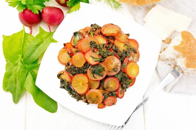 Radieschen mit spinat und gewürzen in einem teller gedünstet