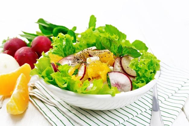 Radieschen-, zwiebel- und orangensalat mit minze, pflanzenöl und gewürzen auf salat in einem teller
