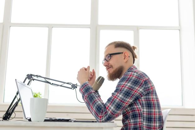 Radio, dj, blogging und people-konzept - lächelnder mann, der vor dem mikrofon sitzt und im radio moderiert