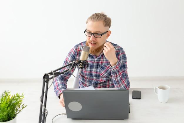 Radio-, dj-, blogging- und people-konzept - lächelnder mann, der vor dem mikrofon sitzt und im radio moderiert