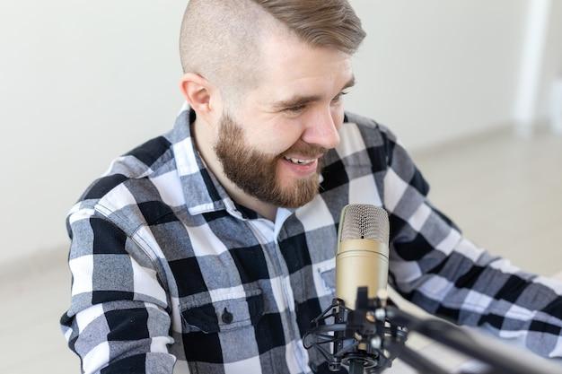 Radio-, dj- und broadcast-konzept - porträt eines hübschen jungen mannes mit blonden haaren, der die show live moderiert