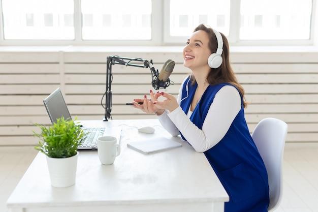 Radio-host-konzept - frau arbeitet als radio-host, der vor dem mikrofon über weiß sitzt