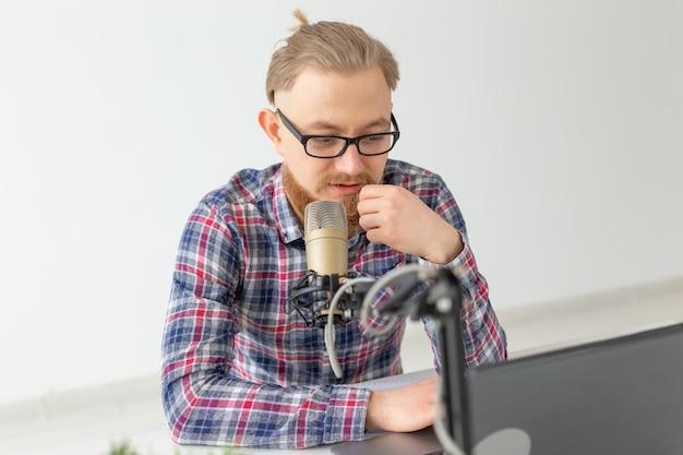 Radio-host-konzept - nahaufnahme eines gutaussehenden mannes, der als radiomoderator bei radiosender arbeitet