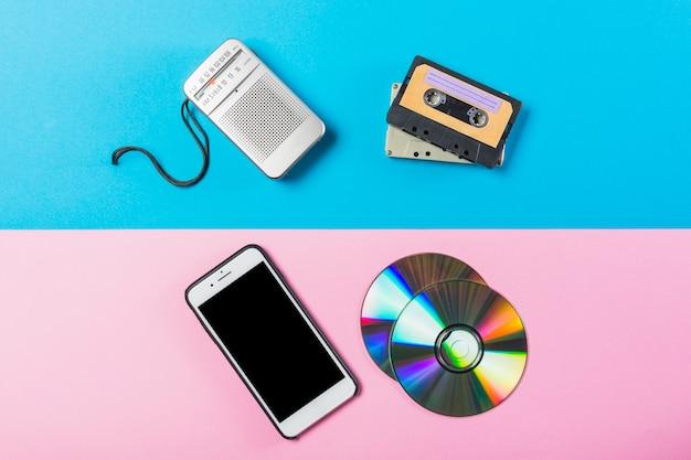 Radio; kassette; cd und handy auf zwei rosa und blau farbigen hintergrund