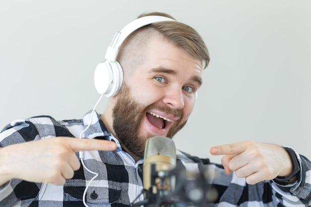 Radio- und dj-konzept - mann mit mikrofon und großem kopfhörer lächelt