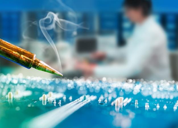 Radioelektronik reparaturhintergrund mit lötmittel über motherboard, reparaturtechnologie unscharf.