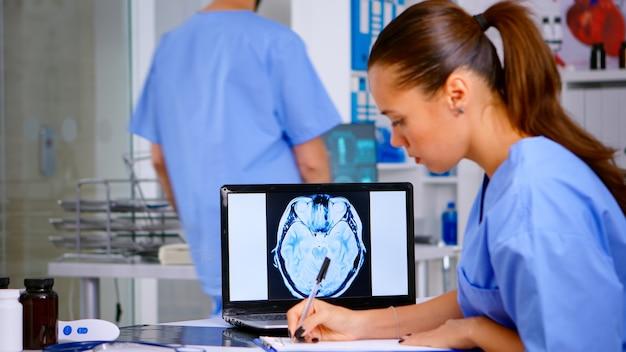 Radiologe, der röntgenfilm analysiert und diagnose in der zwischenablage in der krankenhausklinik schreibt, um die behandlung des patienten zu notieren. assistenzarzt in medizinischer uniform, der digitales röntgen untersucht