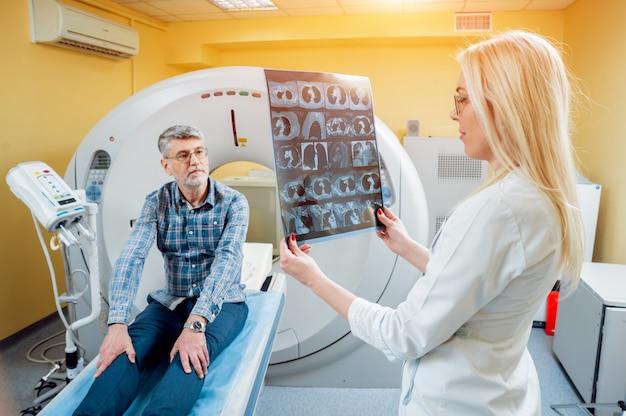 Radiologe mit einem männlichen patienten, der röntgen betrachtet.