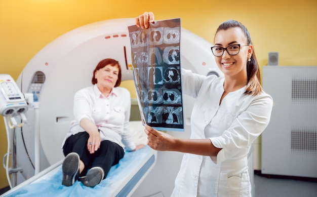 Radiologe mit einer älteren patientin, die röntgen betrachtet.