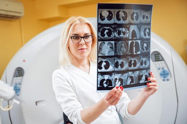 Radiologin, die röntgen im raum der computertomographie betrachtet.