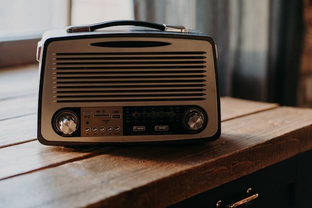 Radiosendung von musik. altes retro-radio im hellen raum auf holztisch. vintage-farbe. musikalische brücke zwischen vergangenheit und zukunft. authentischer retro-look