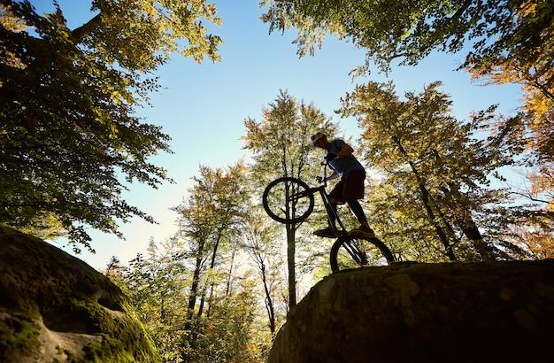 Radprofi balanciert auf trial-fahrrad bei sonnenuntergang