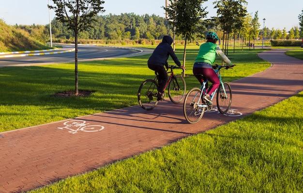 Radweg im öffentlichen park der stadt mit zwei radfahrern, die am frühen morgen fahren. aktiver lebensstil.