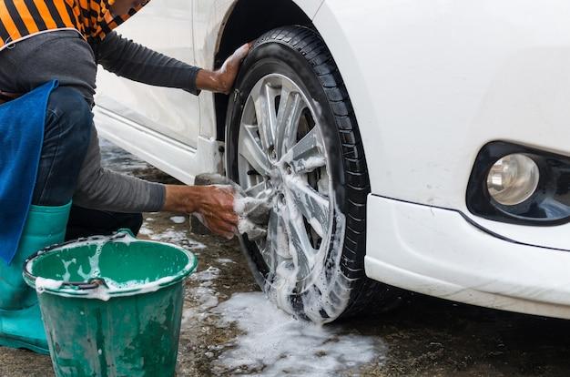 Räder des arbeitskraftwaschwagens auf einem traditionellen autowäschesystem