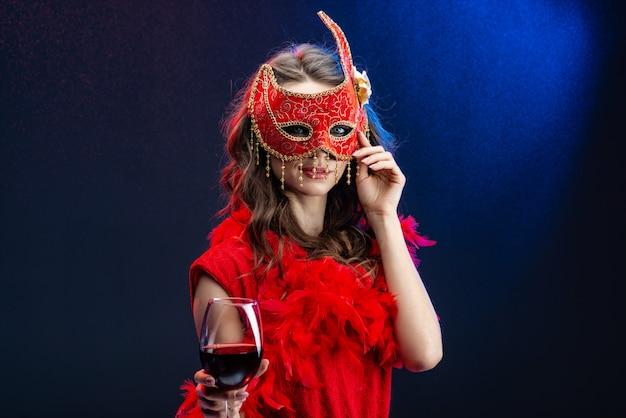 Rätselhafte junge frau in einer roten karnevalsmaske und -boa mit einem angehobenen glas wein