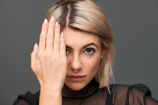 Rätselhafte trendige junge europäische frau mit blond gefärbten haaren und kristallen im gesicht als teil des make-ups, ein auge mit handfläche bedeckend, polierte nägel zeigend. kunst und kosmetik