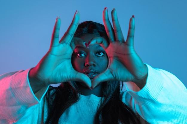 Rätselhafter anblick. brustbild der jungen afrikanischen hübschen frau einzeln auf violettem studiohintergrund. konzept der menschlichen emotionen, gesichtsausdruck, schönheit, mode, jugend, verkauf. körperpositiv