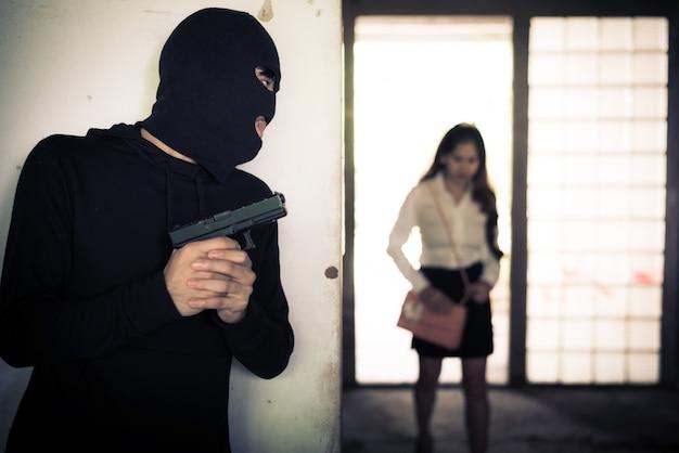 Räuber, der frau hochhält und wartet, um ihre brieftasche oder handtasche durch handgewehr in der ecke des gebäudes zu stehlen