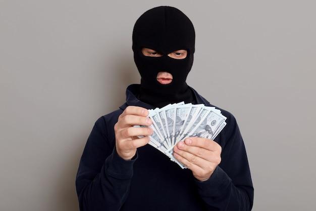 Räuber in schwarzem hoodie gekleidet steht mit verkleidetem gesicht und hält viel geld in den händen