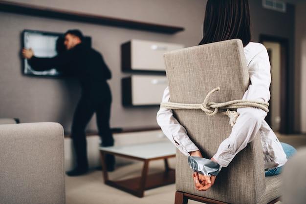 Räuber in schwarzer kleidung auf der suche nach einem safe hinter dem fernseher im haus gegen ein weibliches opfer, das mit seil und klebeband am stuhl festgebunden ist.