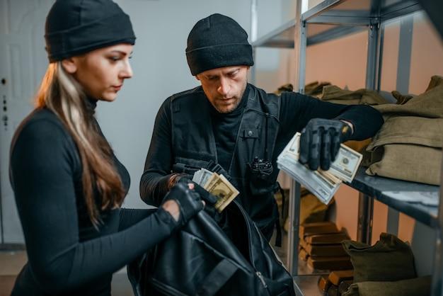 Räuber in schwarzer uniform stehlen geld aus dem tresor