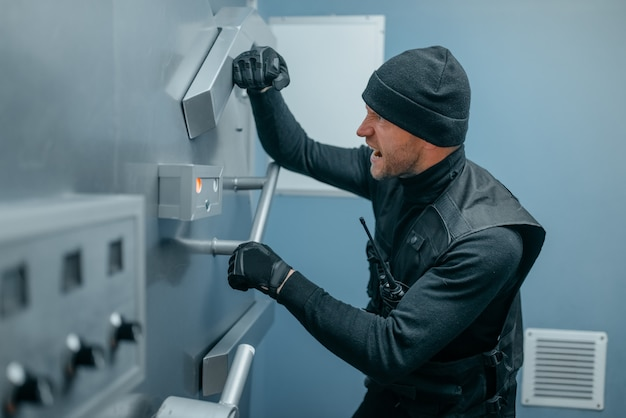 Räuber in schwarzer uniform versuchen, das tresorschloss zu öffnen