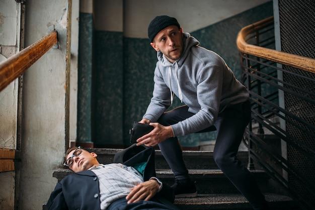 Räuber tötet sein opfer und nimmt eine handtasche in den eingang. theif begeht einen raubangriff auf einen mann. verbrechenskonzept