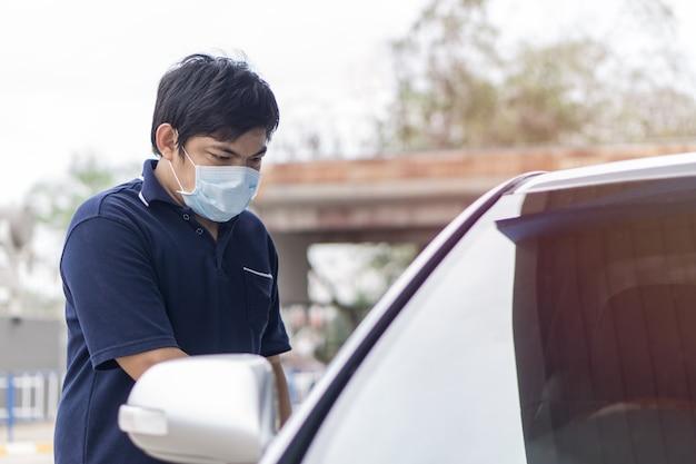 Räuber und der autodieb in einer maske öffnet die tür des autos und entführt das auto.