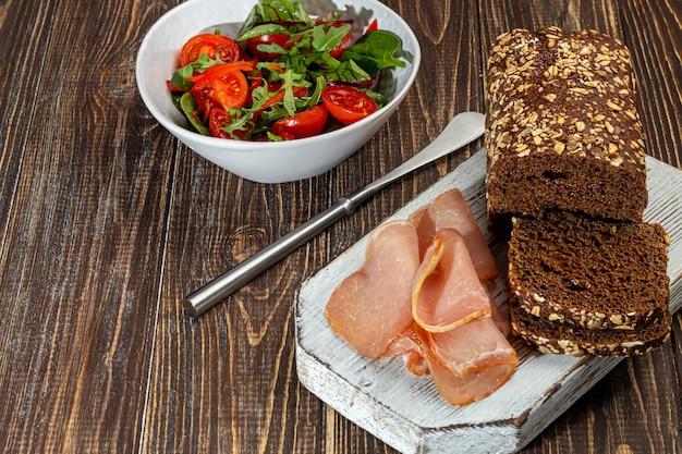 Räucherfleisch auf einem brett mit roggenbrot schneiden. ein sandwich machen. auf einem hölzernen hintergrund. speicherplatz kopieren.