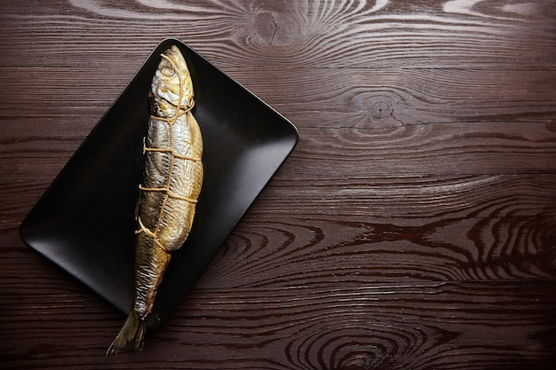 Räucherhering. schnur gebundener fisch auf schwarzem teller auf braunem hölzernem hintergrund mit kopienraum, draufsicht. heiß geräucherter fisch